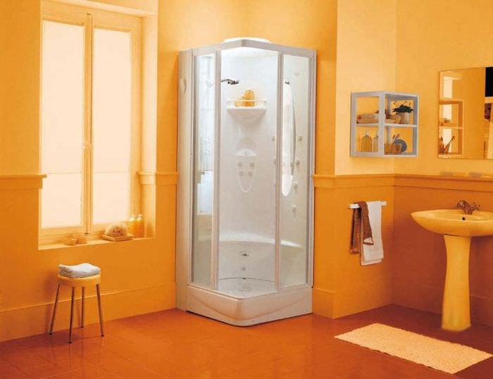 Маленькая ванная комната в оранжевом цвете с угловой душевой кабиной