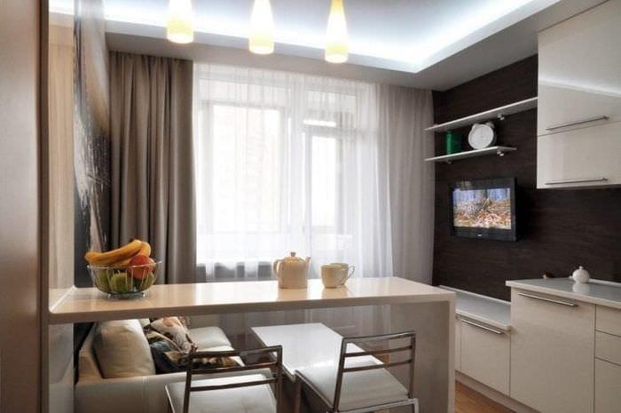 Идея интерьера кухни-гостиной с разделением зон с помощью стола