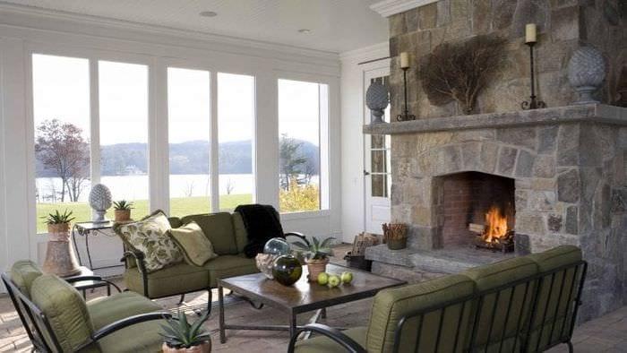 Интерьер просторной гостиной с витражными окнами и камином