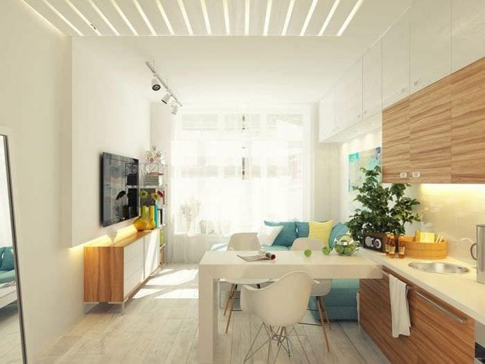 Небольшая светлая кухня гостиная с белым диваном