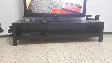 Темная стильная тумба под телевизор для декора комнаты