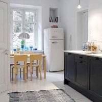 небольшой холодильник в интерьере кухни в темном цвете картинка