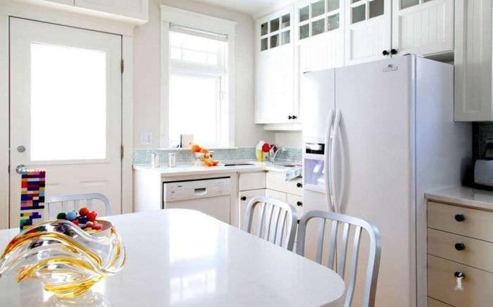 небольшой холодильник в фасаде кухни в стальном цвете