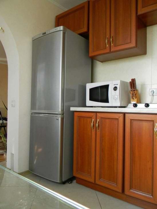 большой холодильник в дизайне кухни в черном цвете