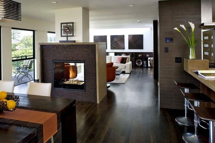 интерьер гостиной с кухней и камином