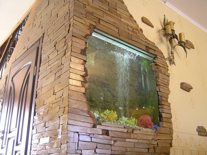 Аквариум в стене прихожей, облицованной камнем