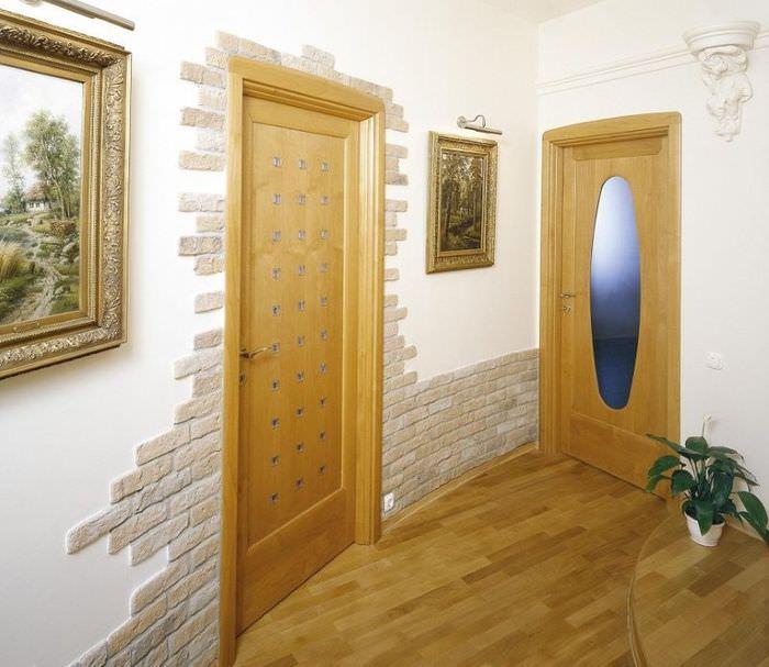 Отделка камнем входной двери и нижней части стены в прихожей