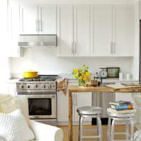 Белый гарнитур и деревянный столок в дизайне кухни