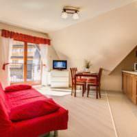 Красный диван и коричневый гарнитур в совмещенной кухне