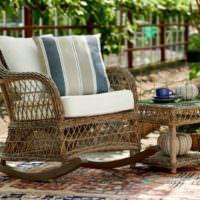 Кресло-качалка из ротанга на дачной террасе