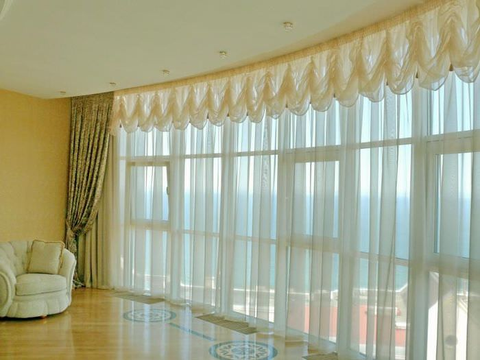 Панорамное окно в гостиной с французскими шторами