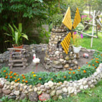 Самодельная мельница из камня на садовой клумбе