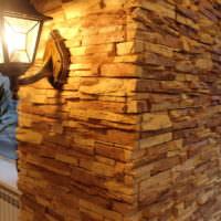 Светильник на стене в прихожей, облицованной камнем