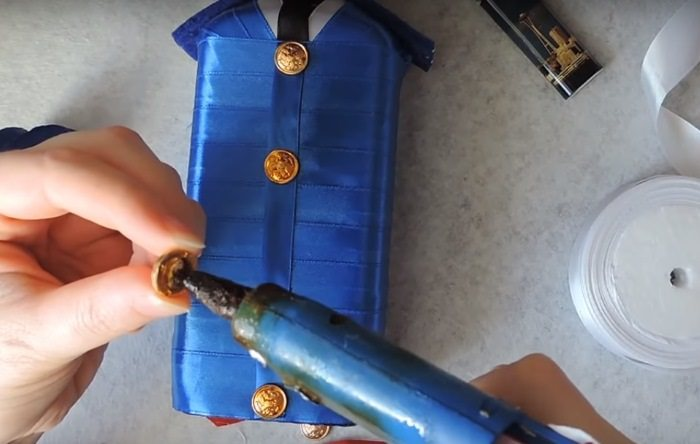 Закрепление пуговицы на бутылке коньяка