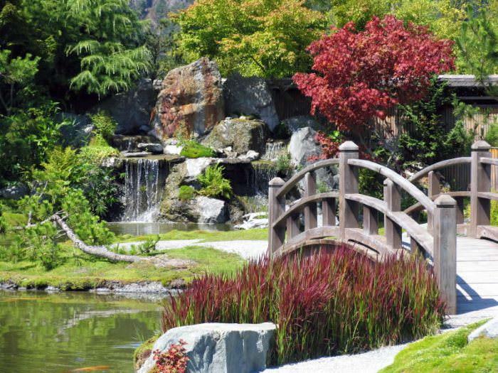 Водопад из камня и деревянный мостик в китайском саду