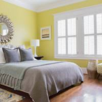 Желтые стены и серое покрывало в спальне 12 кв м