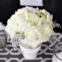 Праздничный букет из белых цветов на столе молодоженов