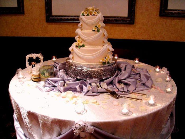 Свадебный торт на столе в окружении свечей