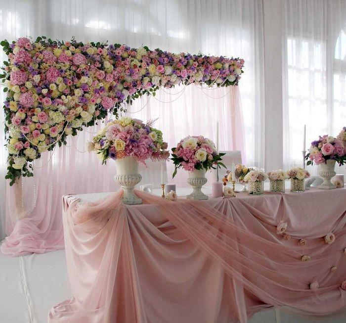 Оформление свадебного стола светлыми цветами и полупрозрачной тканью