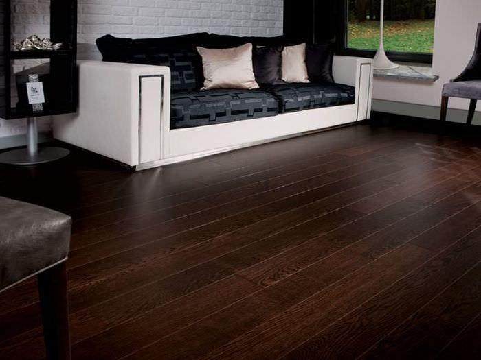 Белый диван на темно-коричневом линолеуме