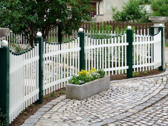 Белый деревянный забор вдоль приусадебного участка