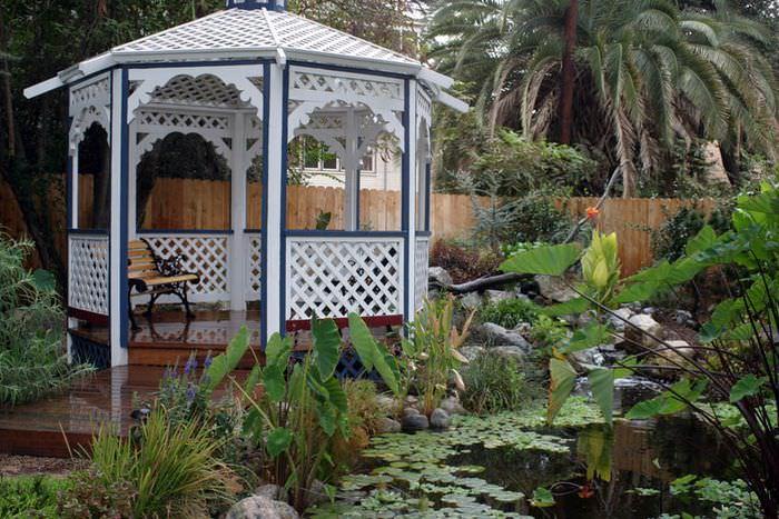 Деревянная беседка и искусственный пруд в дизайне сада