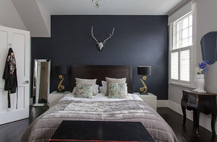 Спальня с темной кроватью и светлым покрывалом