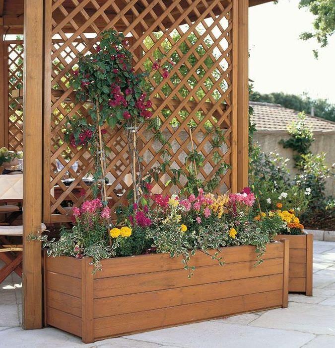 Ящик с цветами у стены деревянной беседки