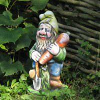 Самодельный гномик с морковкой в оформлении сада