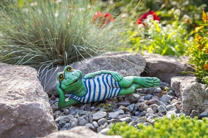 Фигурка лягушонка из мультфильма в декоре сада