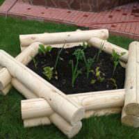 Шестиугольная клумба из бревен для украшения сада
