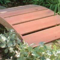 Простой деревянный мостик через садовый ручей