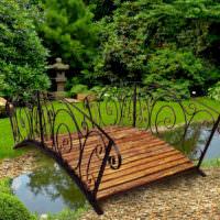 Деревянный мостик с кованными перилами над садовым водоемом