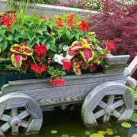 Клумба-телега с цветами в декорировании садового водоема
