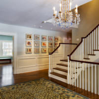 Деревянная лестница с белыми перилами в фойе загородного дома