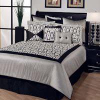 Черная кровать с белым покрывалом в спальне городской квартиры