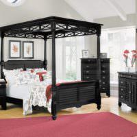 Черная кровать с балахоном в светлой спальне