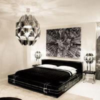 Черная кровать с белыми подушками в светло-серой комнате