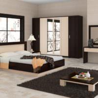 Низкая кровать и темный коврик на полу спальни