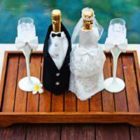Свадебные бутылки шампанского на деревянном подносе