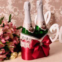 Пара свадебных бутылок, перевязанных красной лентой
