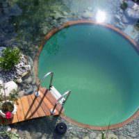 Круглый бассейн с деревянным мостиком
