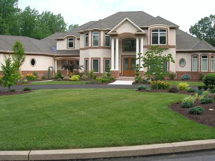 Зеленый газон английского типа перед фасадом загородного дома