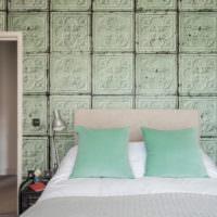 Белое покрывало и мятные подушки в интерьере спального помещения