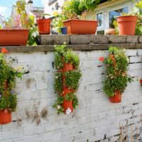 Декорирование кирпичного забора горшками с цветами