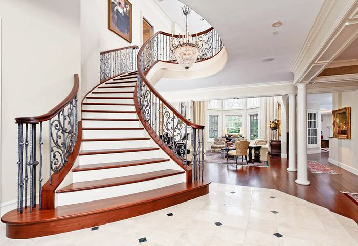 Интерьер холла загородного дома с лестницей в классическом стиле