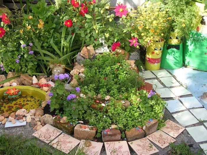 Клумба с цветами из старого кирпича и других строительных отходов