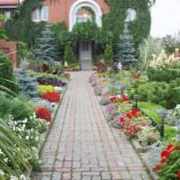 Рабатки из цветов по краям мощенной дорожки