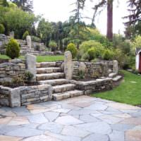 Террасы из природного камня на участке со склоном