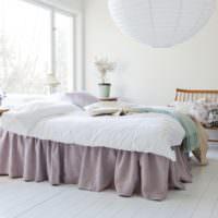 Белая спальня с лавандовым покрывалом на кровати